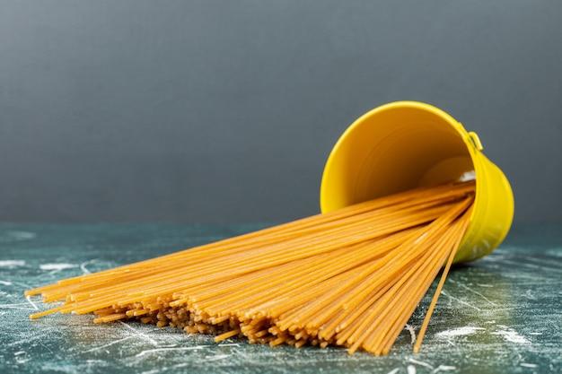 Ongekookte volkoren pasta spaghetti in een omgekeerde emmer op het blauwe oppervlak