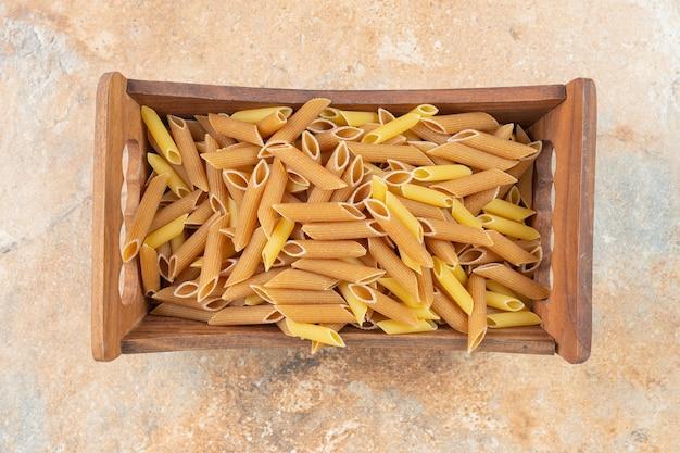 Ongekookte volkoren penne pasta in een houten kist op het marmeren oppervlak