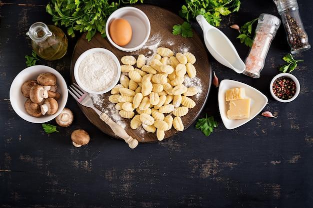 Ongekookte zelfgemaakte gnocchi met een champignonroomsaus en peterselie in kom op een donkere achtergrond.