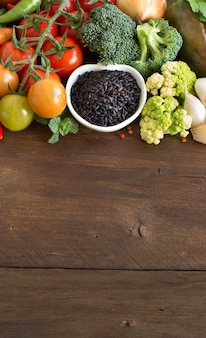 Ongekookte zwarte rijst in een kom met groenten op hout met exemplaarruimte