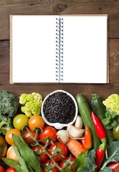 Ongekookte zwarte rijst met groenten en notitieboekje op hout