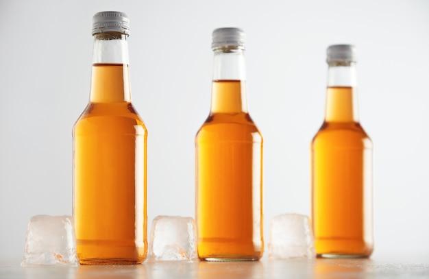 Ongelabelde rustieke flessen verzegeld met een lekker koud drankje erin gepresenteerd naast grote ijsblokjes