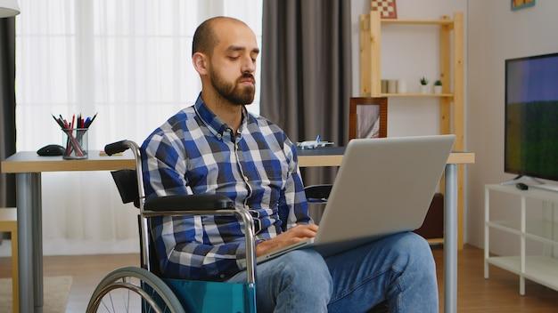 Ongeldige freelancer in rolstoel die op afstand op laptop werkt.