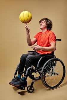 Ongeldige man draait de bal op zijn vinger, lacht, lacht alleen zittend op rolstoel, geïsoleerd op beige achtergrond
