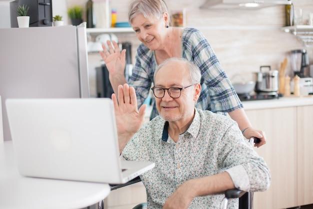 Ongeldige man en vrouw zeggen hallo tegen hun familie. gehandicapte senior man in rolstoel en zijn vrouw hebben een videoconferentie op laptop in de keuken. verlamde oude man en zijn vrouw hebben een online conferentie