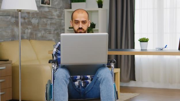 Ongeldige man in rolstoel die vanuit huis aan laptop werkt.