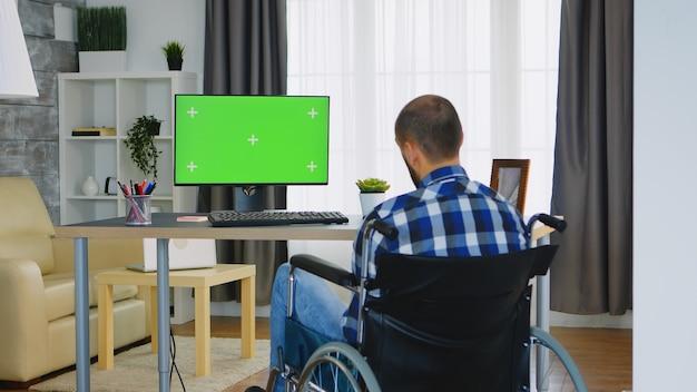 Ongeldige man in rolstoel werken op computer met groen scherm.