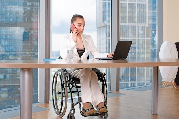 Ongeldige of gehandicapte jonge zakelijke vrouw persoon zit rolstoel werken in kantoor op een laptop