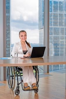 Ongeldige of gehandicapte jonge zakenvrouw zitten rolstoel werken in kantoor op een laptop