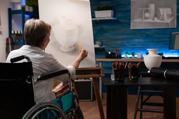 Ongeldige oude kunstenaar die vaas op canvas tekent met potlood