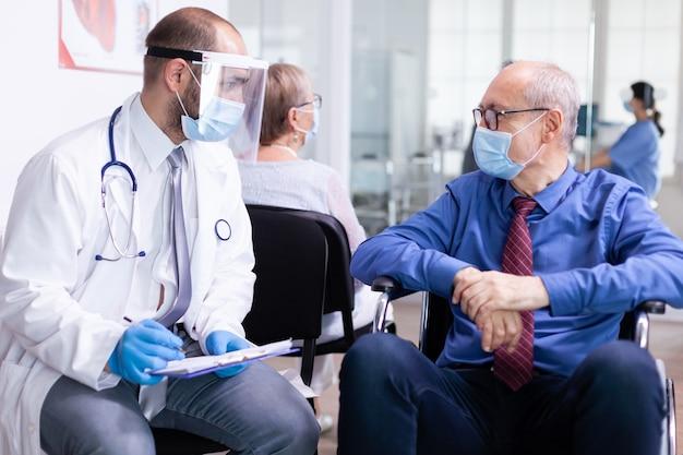 Ongeldige oude man met gezichtsmasker tegen infectie met coronavirus in rolstoel in gesprek met arts in wachtruimte van ziekenhuis
