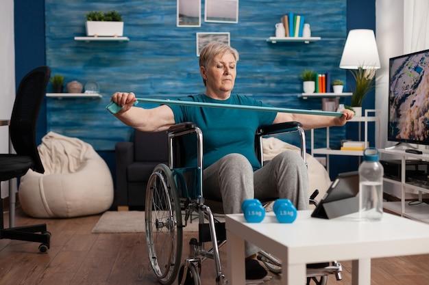 Ongeldige oude vrouw in rolstoel die de weerstand van de arm uitrekt en de lichaamsspier traint met behulp van een elastische band na een beenongeval tijdens het kijken naar therapievideo op tablet. gepensioneerde die gymnastiektraining in woonkamer uitoefent