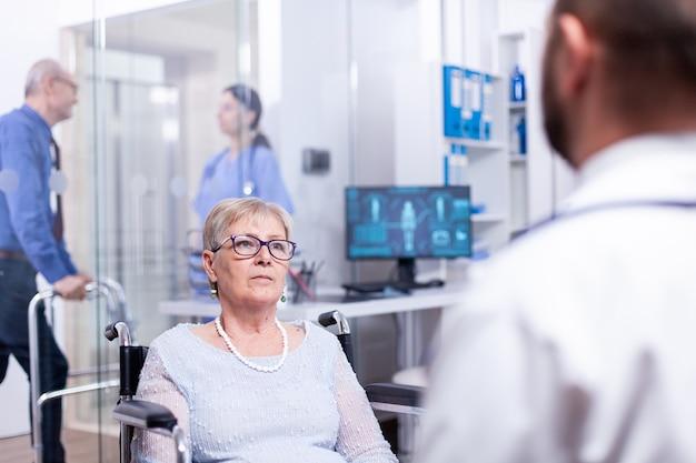Ongeldige oude vrouw zit in een rolstoel luisterende arts die de medische diagnose in de ziekenhuiskamer uitlegt