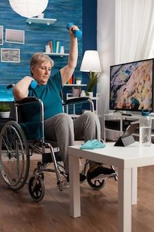 Ongeldige senior vrouw met workout dumbbells die de arm opheft tijdens het uitoefenen van de volharding van de lichaamsspieren door cardio-oefening te doen