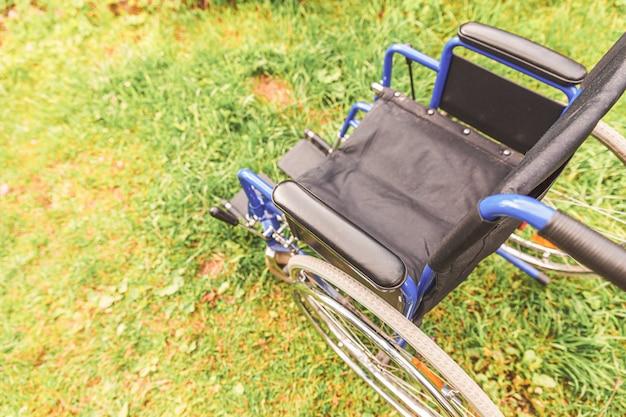 Ongeldige stoel voor mindervaliden die buiten in de natuur geparkeerd staat