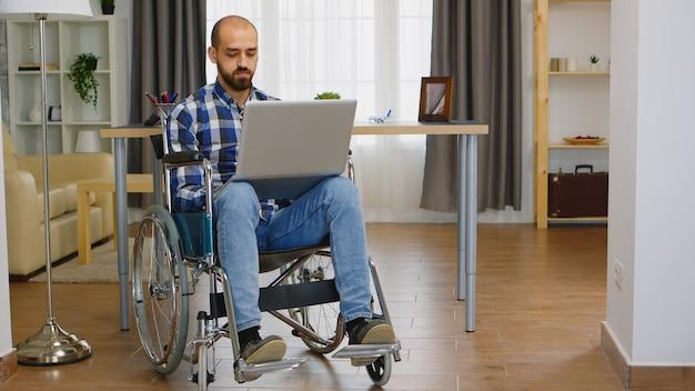 Ongeldige zakenman in rolstoel die op laptop werkt vanuit kantoor aan huis.