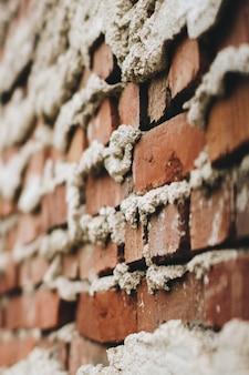 Ongelijk gebouwde bakstenen muur met cement dat uit de scheuren komt