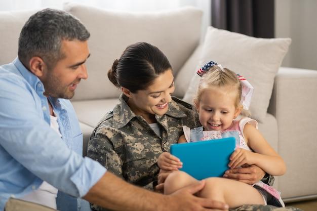 Ongelofelijk blij. militaire vrouw voelt zich ongelooflijk gelukkig bij het kijken naar tekenfilms met dochter en echtgenoot