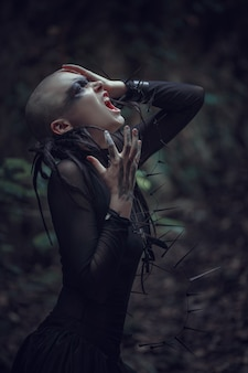 Ongelofelijk prachtig meisje in een zwarte jurk. artistieke fotografie. mooie kale vrouw op een mystiek landschap