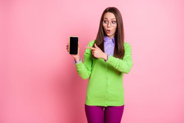 Ongelooflijk apparaat. verbaasd meisje wijsvinger smartphone dragen broek geïsoleerde pastel kleur achtergrond