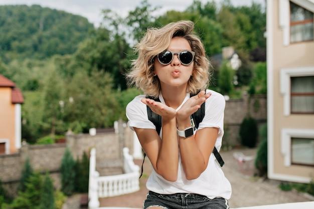 Ongelooflijk effectief charmant meisje met kort krullend kapsel in zwarte zonnebril die een kus verzendt