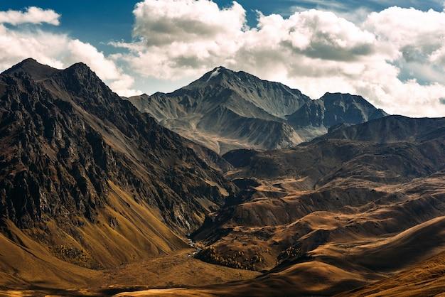 Ongelooflijk mooi berglandschap. bergtoppen in de zon. panoramisch uitzicht op de herfstbergen. landschap met uitzicht op bergdalen. bovenaanzicht van de bergkloof. ruimte kopiëren