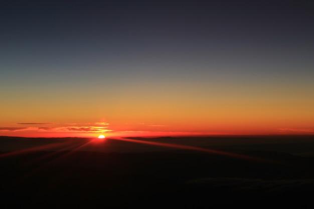 Ongelooflijk uitzicht op zonsopgang boven de wolken gezien vanuit vliegtuigvenster tijdens de vlucht