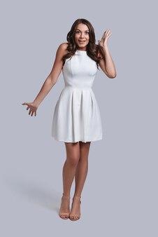 Ongelooflijk! volledige lengte van een verraste jonge vrouw in een witte jurk die naar de camera kijkt en een gezicht trekt terwijl ze tegen een grijze achtergrond staat