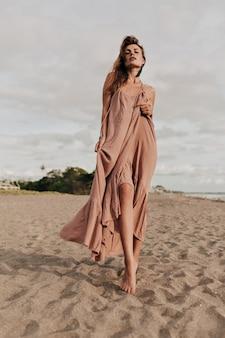 Ongelooflijk vrouwelijk model met lang haar dat een lange jurk draagt op het strand in zonlicht door de oceaan