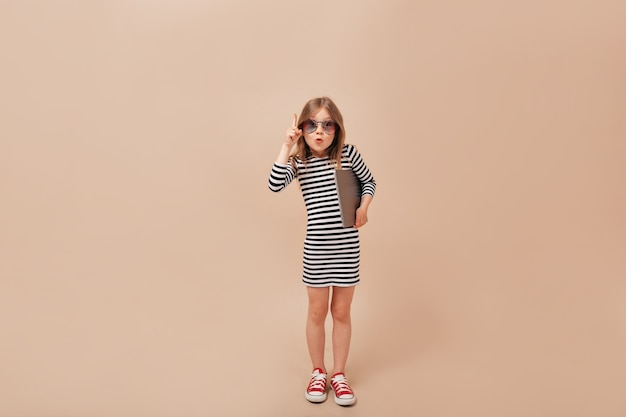 Ongelooflijke charmante kleine dame die kleding en sneakers draagt die over geïsoleerde achtergrond met laptop stellen en duimen opdagen