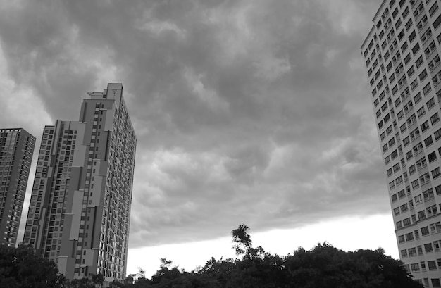 Ongelooflijke donkergrijze nimbuswolken boven wolkenkrabbers voor de zware regen in zwart-wit