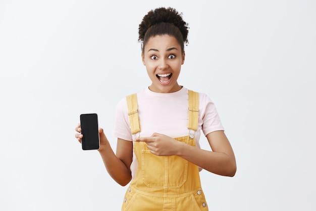 Ongelooflijke prijs voor een ongelooflijke telefoon. verbaasd en opgewonden aantrekkelijk afrikaans-amerikaans meisje met gekamd haar in gele overall, wijzend naar links op smartphone, apparaatscherm toont