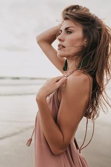 Ongelooflijke stijlvolle vrouw in zomerjurk poseren door de oceaan in warme zomerdag