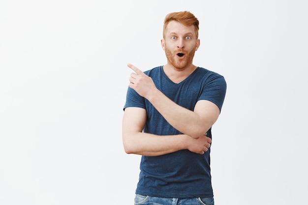 Ongelooflijke uitstraling op die manier. onder de indruk en gelukkig knappe roodharige man met baard in blauw t-shirt, wijzend naar de linkerbovenhoek, hijgend van verbazing en verrassing, geïnteresseerd over grijze muur