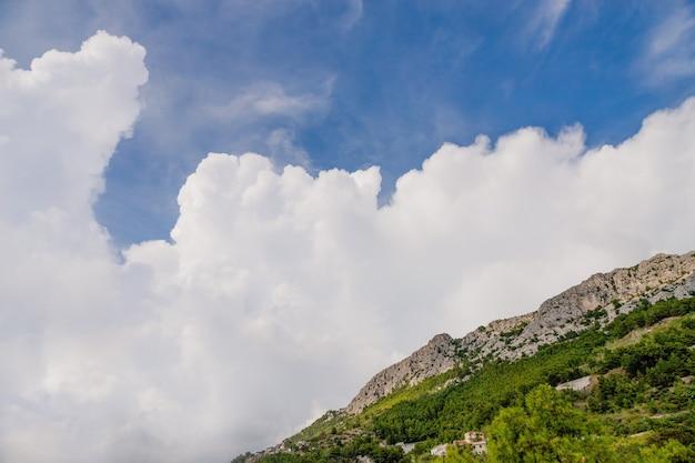 Ongelooflijke witte grote wolk en bergen in brela, kroatië