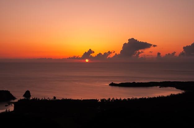 Ongelooflijke zonsondergang met een prachtig uitzicht op het strand van tudumari in de vorm van een halve maan levendige kleuren roze, geel en oranje.