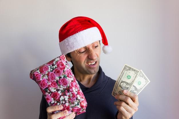 Ongelovige jonge man met kerstmuts met ingepakt cadeau en weinig geld met een sceptische blik