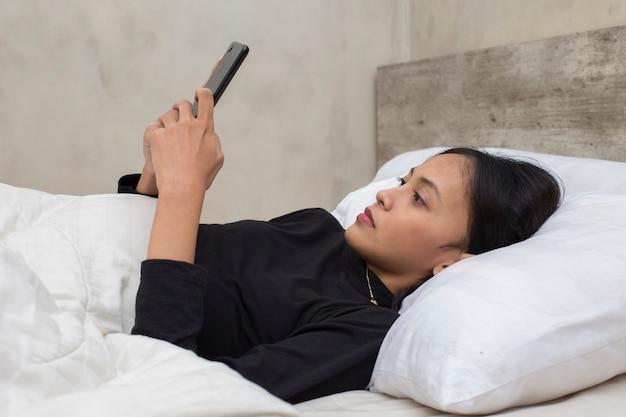 Ongelukkig aziatisch mooi meisje verdrietig met smartphone op bed