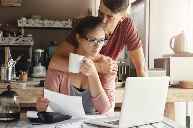 Ongelukkig blanke gezin met economische problemen. ondersteunende jonge man die probeert zijn bezorgde vrouw op te vrolijken in een bril die zich gestrest voelt, geconfronteerd met een financieel probleem