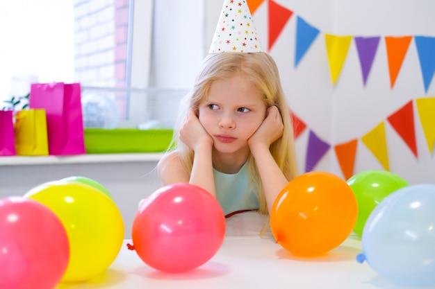 Ongelukkig blond kaukasisch meisje met saai gezicht in de buurt van verjaardag regenboogcake. feestelijke kleurrijke achtergrond. slecht verjaardagsfeestje