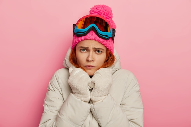 Ongelukkig boze jonge vrouw ontevredenheid, draagt witte warme jas en handschoenen, beeft van de kou