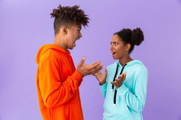 Ongelukkig broer en zus staan samen en ruzie, geïsoleerd over violette muur