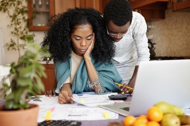 Ongelukkig en gestrest jonge afrikaanse vrouw zit aan de keukentafel met papieren en laptopcomputer, probeert te bezuinigen op de huishoudelijke uitgaven terwijl ze samen met haar man gezinsbudget doet