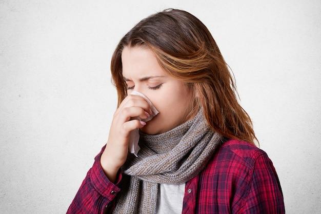 Ongelukkig gefrustreerd vrouwelijk model werd ziek door koud winterweer, niest en heeft loopneus, hoofdpijn