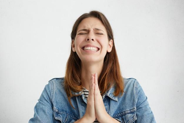 Ongelukkig gestresste jonge vrouw die tot god bidt, iets gulzigs smeekt.