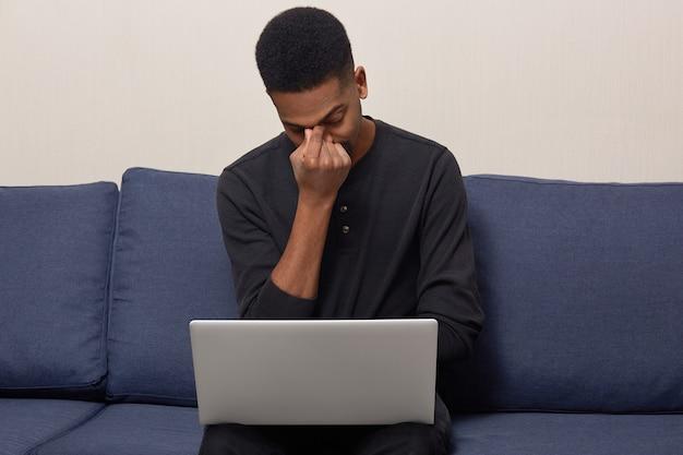Ongelukkig gestreste zwarte jonge volwassen man houdt zijn neus op elkaar, probeert zich te concentreren, gekleed in een zwarte trui, werkt op een laptopcomputer, zit op een comfortabele bank, probeert informatie te verzamelen