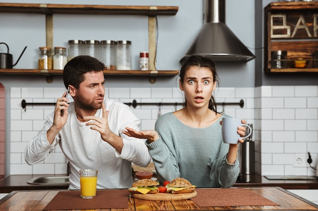 Ongelukkig jong koppel zittend in de keuken tijdens de lunch thuis, met een probleem, mobiele telefoon vast te houden
