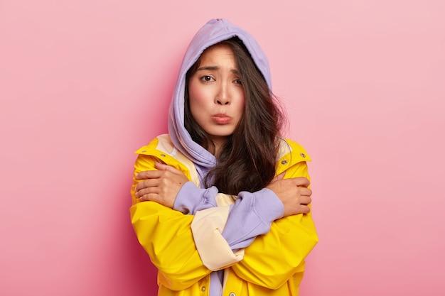 Ongelukkig jong meisje voelt zich eenzaam en koud, kijkt droevig naar de camera, houdt de handen gekruist, draagt een capuchon en regenjas, neerslachtig door slecht weer
