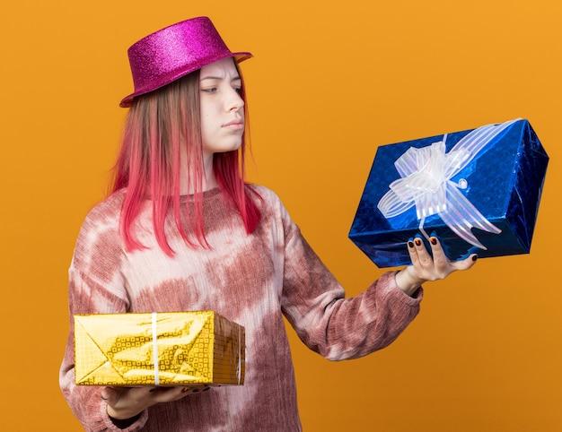 Ongelukkig jong mooi meisje met een feesthoed die vasthoudt en kijkt naar geschenkdozen geïsoleerd op een oranje muur