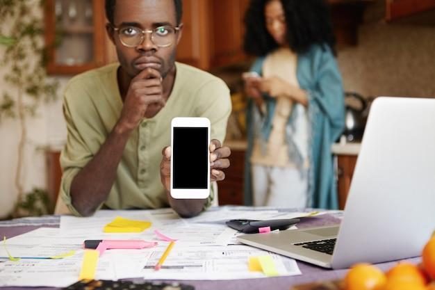 Ongelukkig jonge afrikaanse man in glazen zittend aan tafel met papieren, laptop en rekenmachine tijdens het berekenen van het gezinsbudget, mobiele telefoon te houden